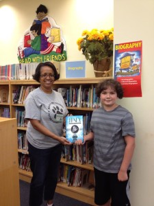 Kyle Driebeek donating a book to his school library